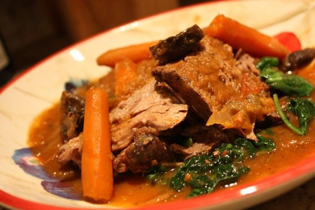 A plate of Beef Pot Roast over a bed of sautéed spinach.