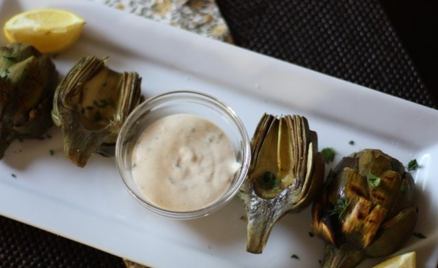 Grilled artichokes served on a white platter with remoulade dipping sauce