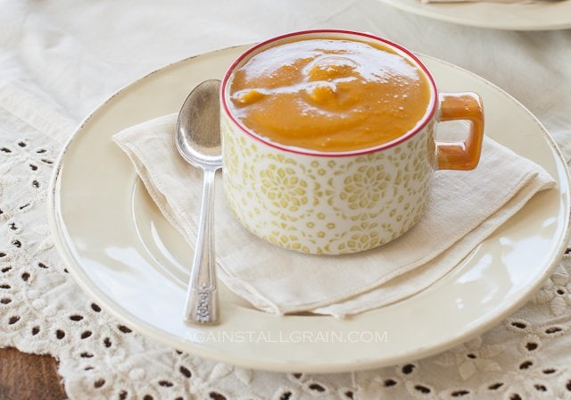 A steaming cup of traditional roasted pumpkin soup that is vegan and dairy free.