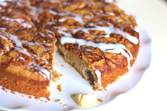 apple spice coffee cake with one piece remove on a white plate and frosting drizzled on top