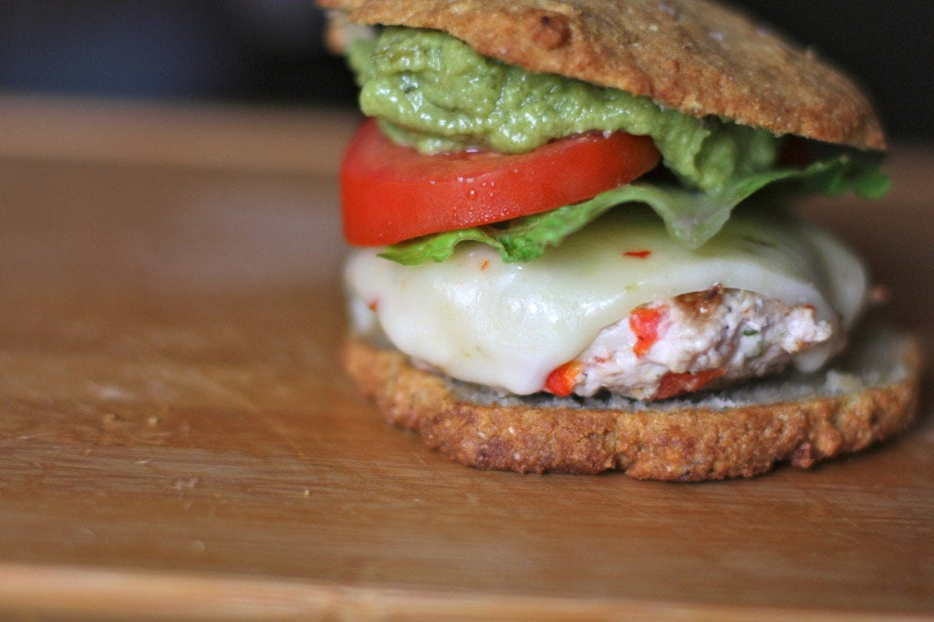 A chili lime chicken burger piled high with fresh guacamole, lettuce, tomato, homemade mayonnaise, and pepper jack cheese.