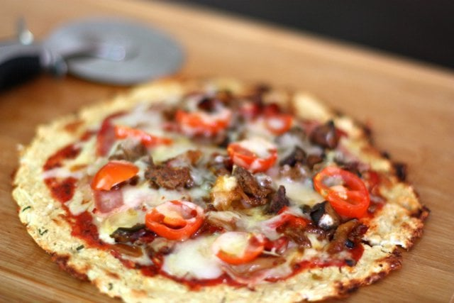 A Cheesy Cauliflower Crust Pizza topped with chorizo sausage, bacon, onions and peppers.