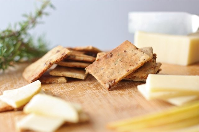 savory and sweet crackers on a cheese board with cut cheese right next to it and a sprig of rosemary in the background