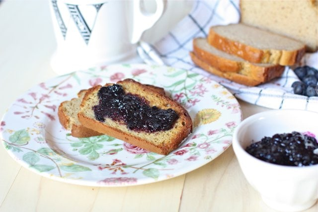Homemade Blueberry Preserves without Pectin on grain free bread on a plate with two slices cut in the background