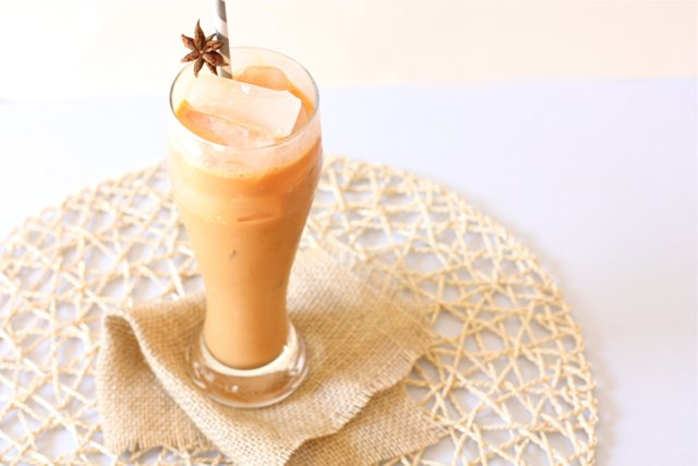 A tall glass Thai Iced Tea brimming with sweetness and creaminess.