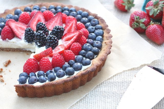 Delicious and sweet red, white and blue berry tart with dairy free vanilla bean custard.