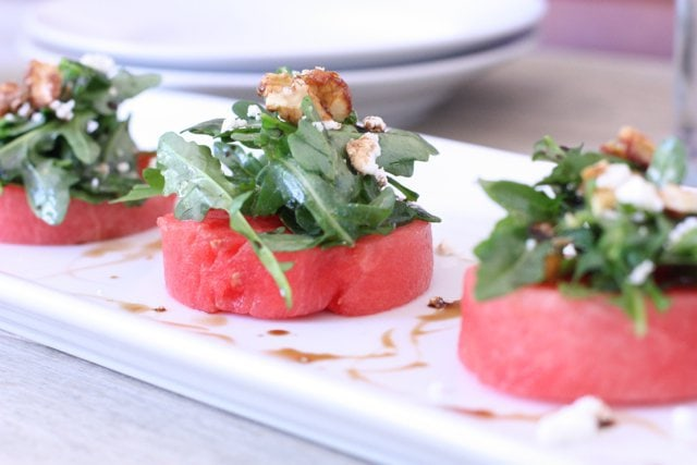 watermelon salad with arugula and goat cheese cut in circles on top of a white dish ready to be served