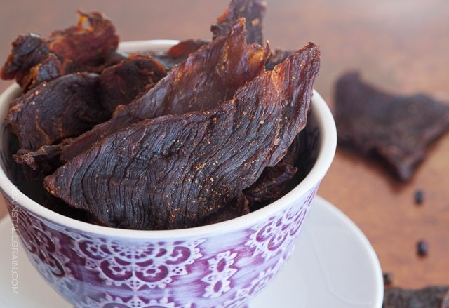 smoky healthy beef jerky sticking out of a decorative cup with some in the background half eaten