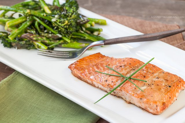 A plate of asian roasted salmon with a side of asparagus and brocollini.