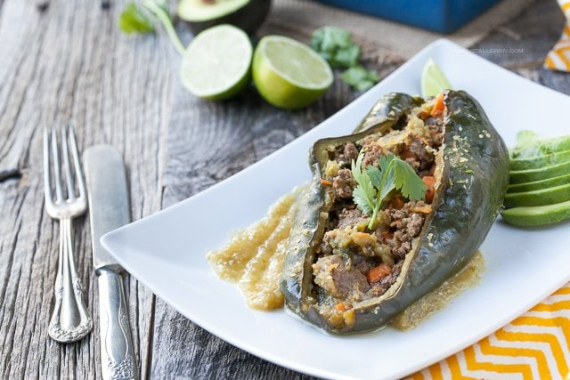 A plate of smokey pablano peppers stuffed with a mix of ground beef, sweet potatoes, carrots, and spinach seasoned with mexican seasonings and homemade tomatillo sauce.