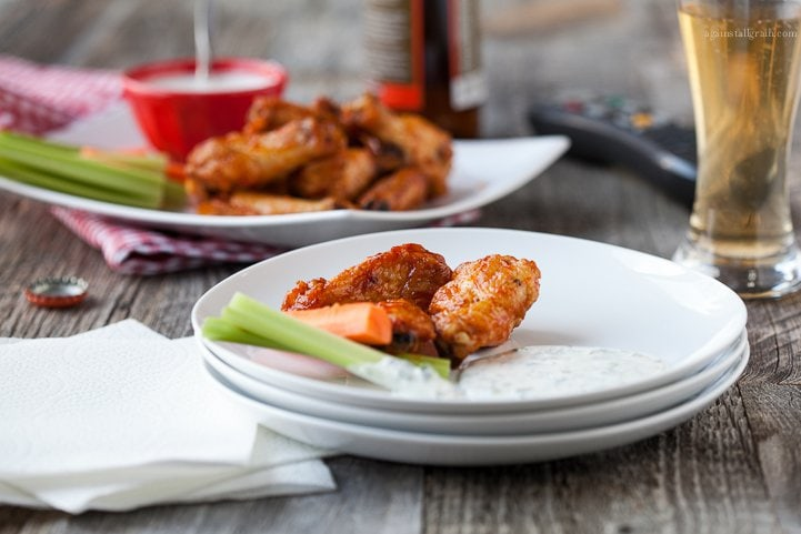 A plate of spicy chicken wings with dairy free ranch dressing.