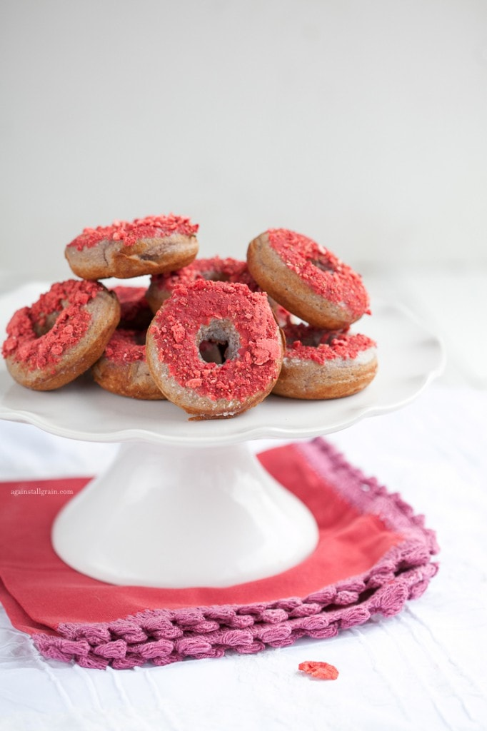 strawberry donuts neatly stacked on a white serving platter