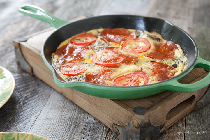 A skillet of Gluten Free, Paleo Pizza Frittata filled with mushrooms, spinach, tomatoes, and pepperoni.