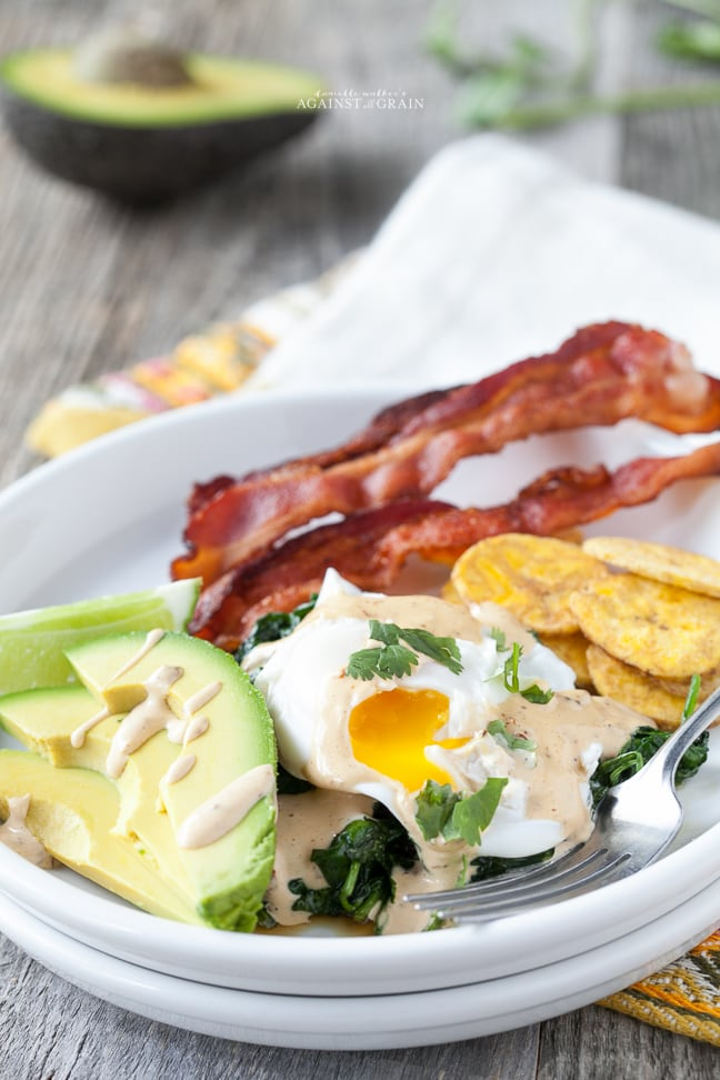 Whole30 friendly Mexican eggs benedict served with fresh avocados, plantains and bacon on a white plate placed on a wooden table.