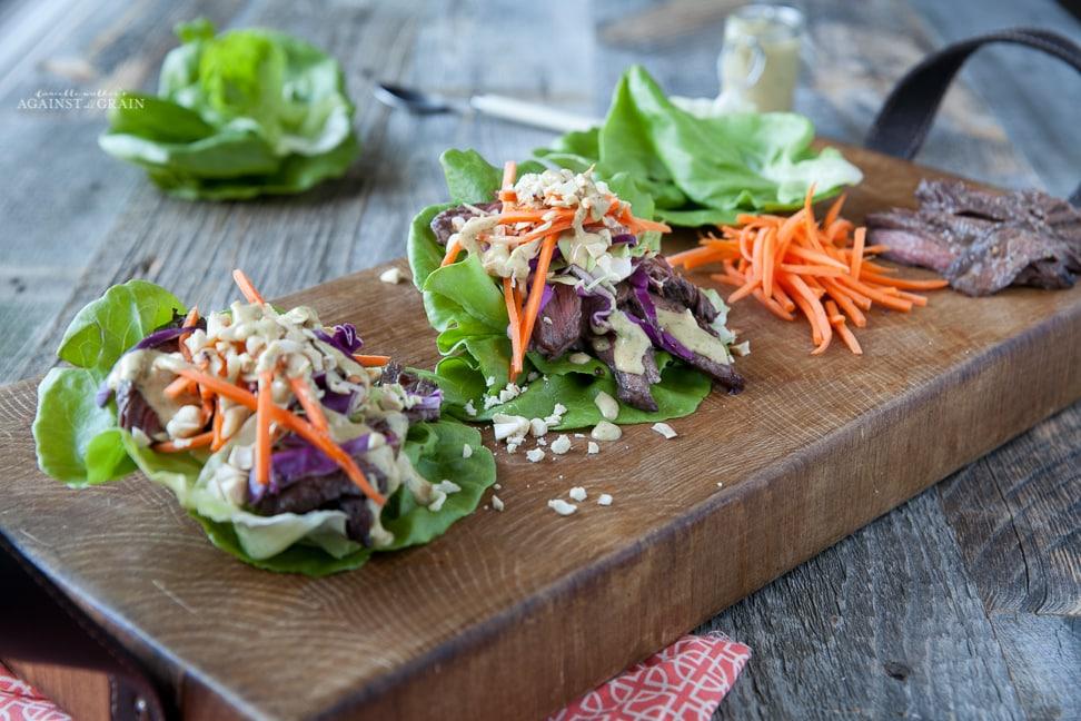 Thai Steak Lettuce Wraps sitting on a wooden cutting board