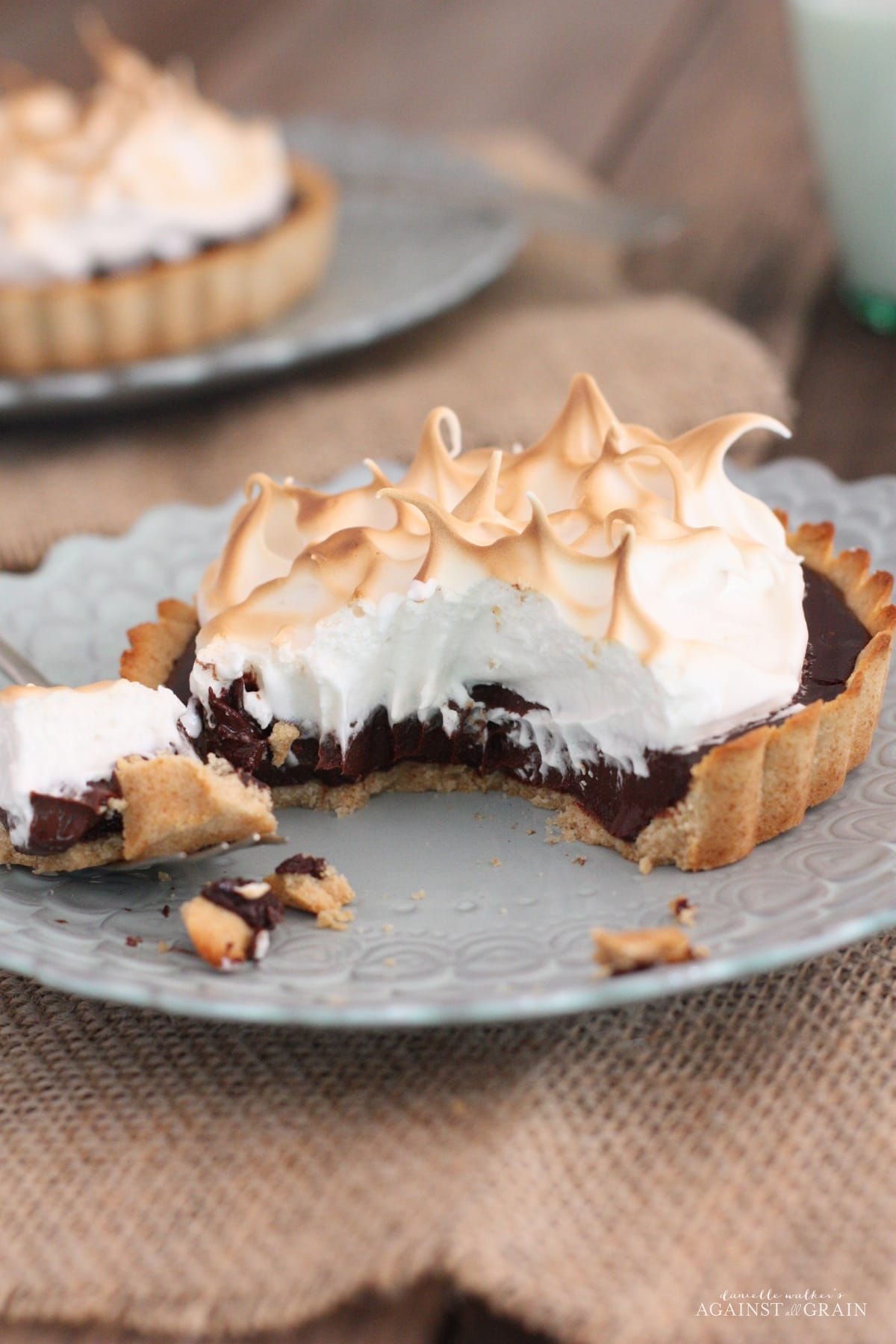 Marshmallow S'more Tart served on a white plate with a scalloped edge design; partially eaten