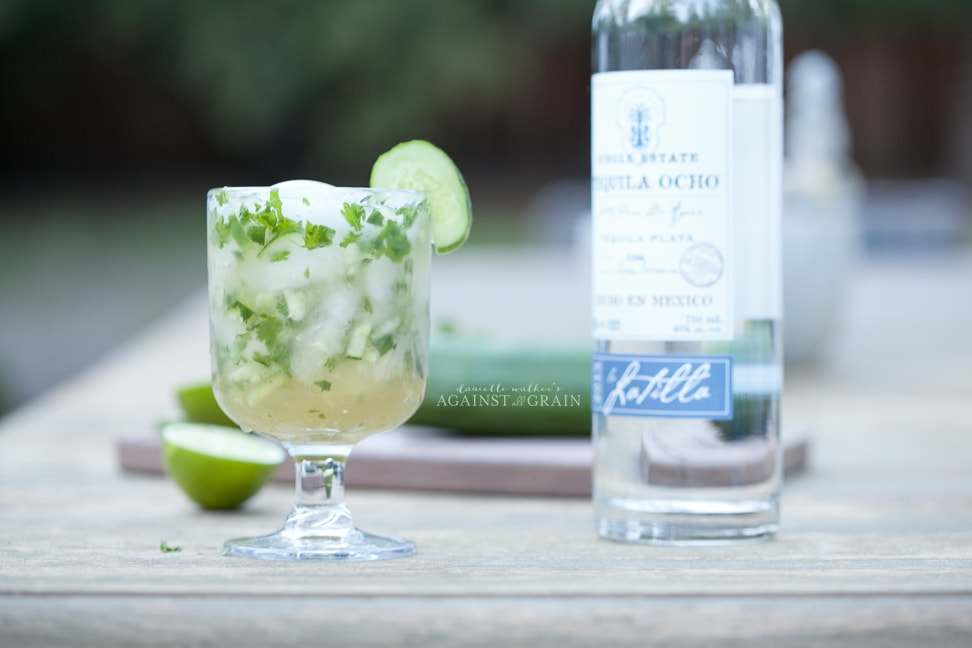 healthy margarita with cucumber and cilantro in a goblet with a lime and a bottle of tequila on the side