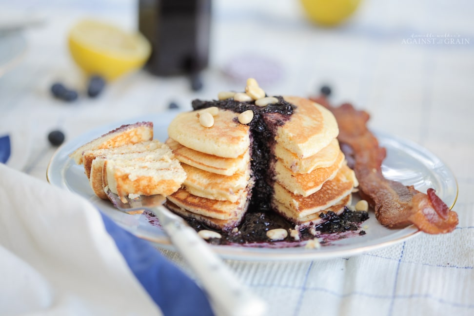 A stack of lemony gluten free pancakes topped with a blueberry sauce.