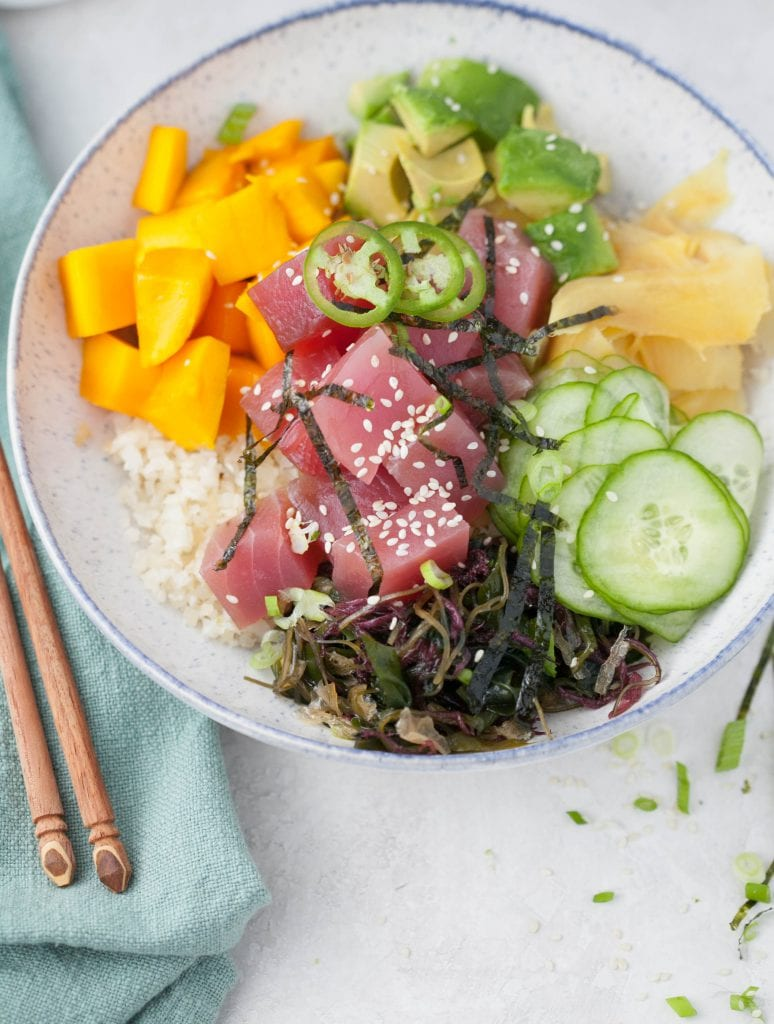 poke bowl with raw tuna, cauliflower rice, avocado, ginger, mango and thin slices of cucumber