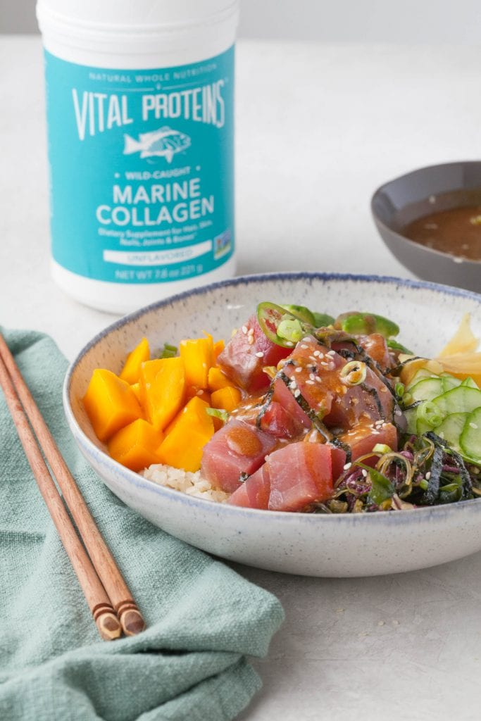 poke bowl with raw tuna, cauliflower rice, avocado, ginger, mango and thin slices of cucumber with a canister of Vital Proteins Marine Collagen in the background