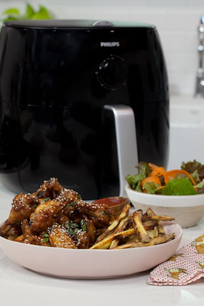 Sticky Sesame Chicken Wings with french fries in a white plate next to a black air fryer