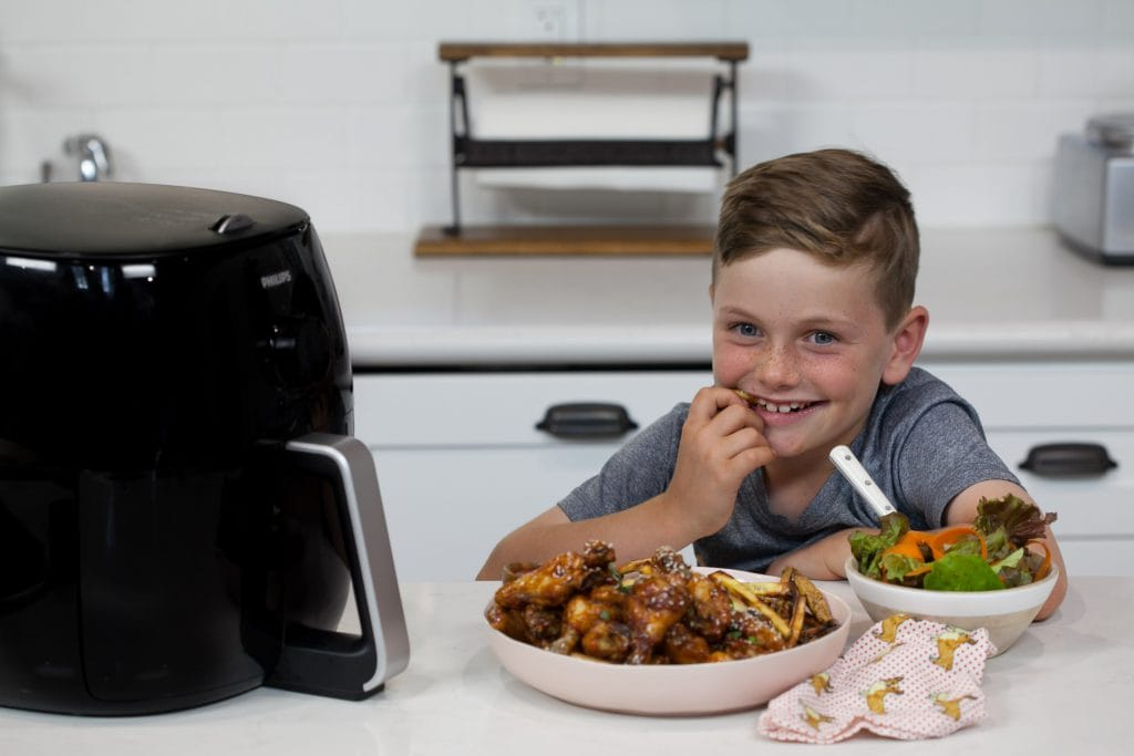 young boy smiles at camera waiting to dive into a bowl of Sticky Sesame Chicken Wings with french fries while he stands in home kitchen next to an air fryer