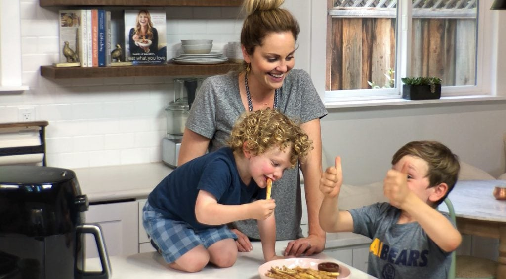 Mother stands in home kitchen with her two sons while they enjoy a plate of air fried french fries