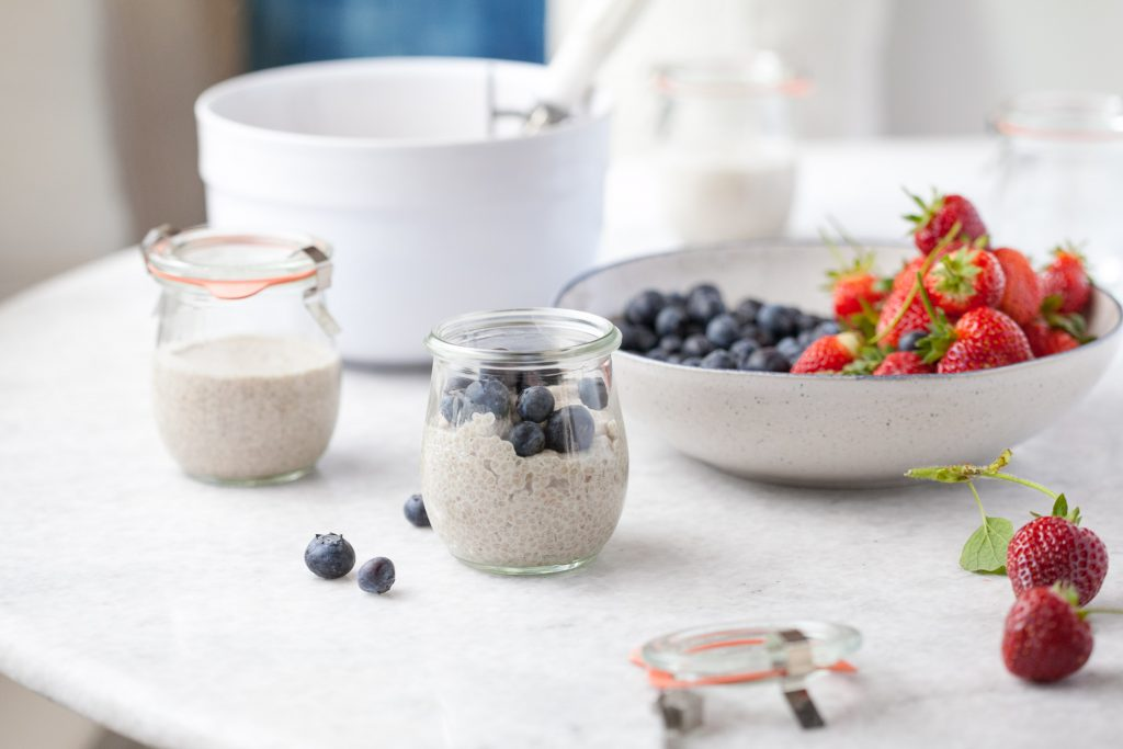 dairy free vanilla chia pudding in a small glass jar with blueberries on top on a table with fresh berries next to it