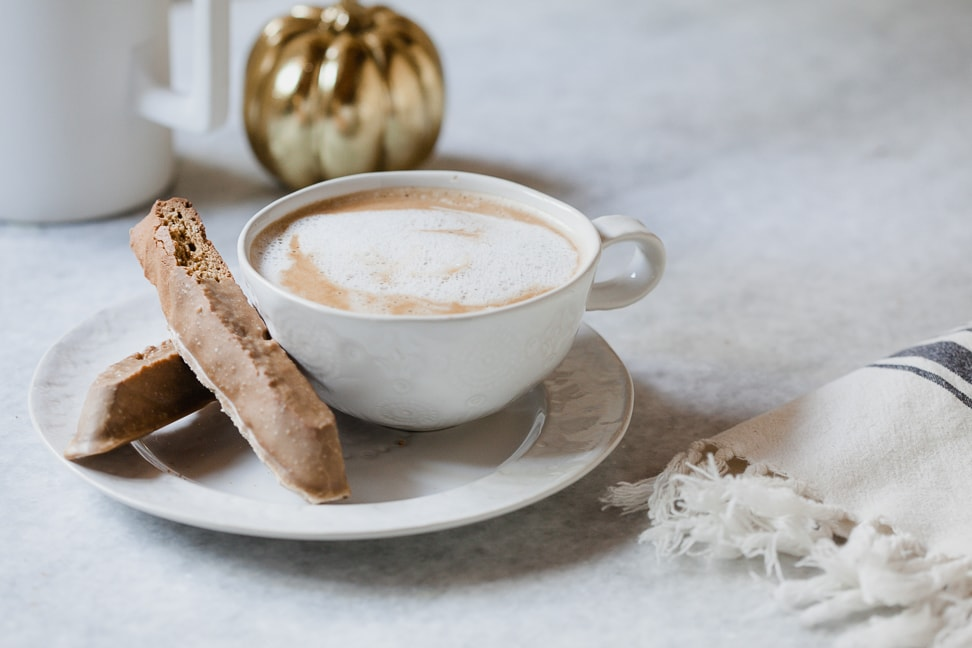 gluten free biscotti next to a latte in a white cup