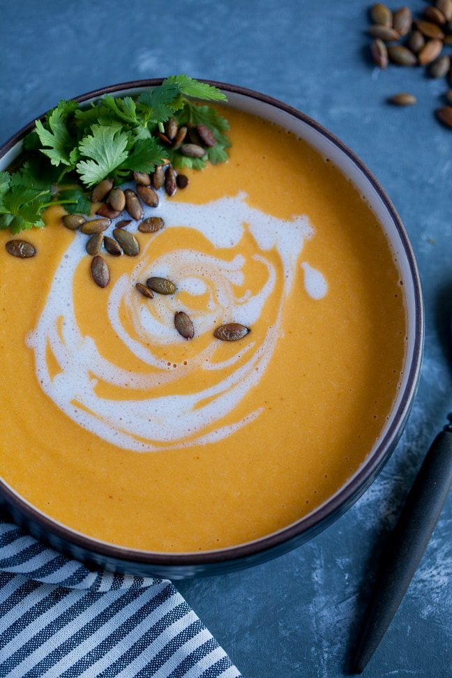 Red Curry Butternut Squash Soup in a black bowl garnished with roasted pipits and cilantro