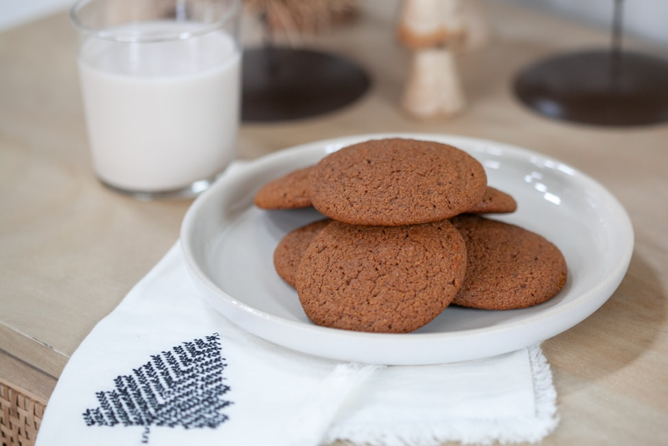 gluten free ginger molasses cookies on plate with a glass of almond milk