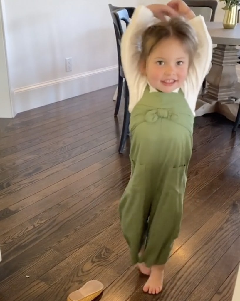 female child wearing an olive green jumpsuit practices ballet while barefoot in her home