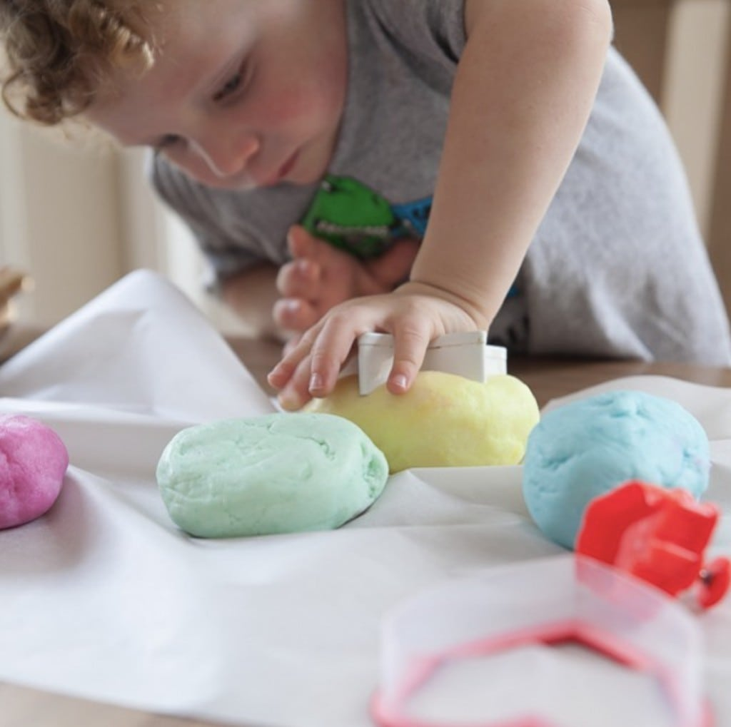 small male child with curly hair uses a cookie cutter to cut into a variety of pastel colored play dough