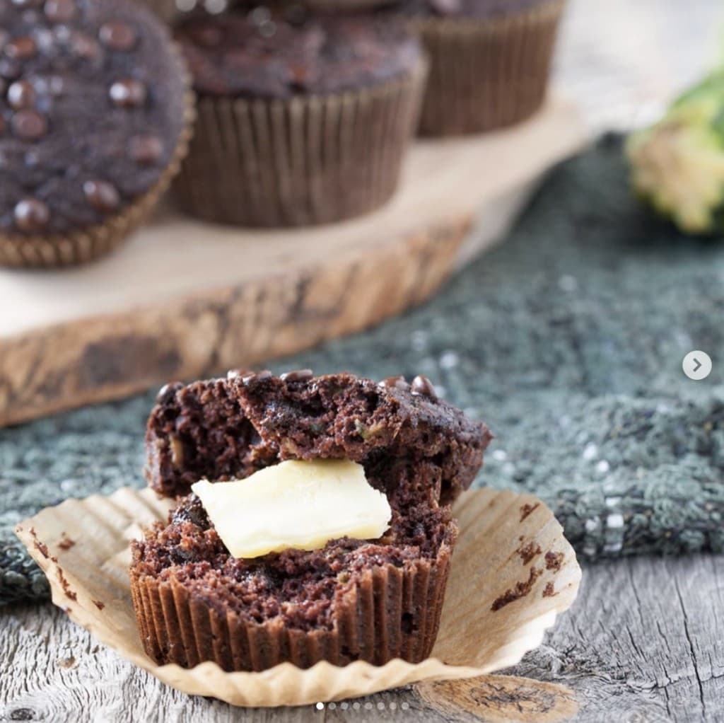 chocolate muffin in parchment cupcake wrapper cut in half with butter in the middle on a wooden surface with a display of chocolate muffins in the background on a wooden platter