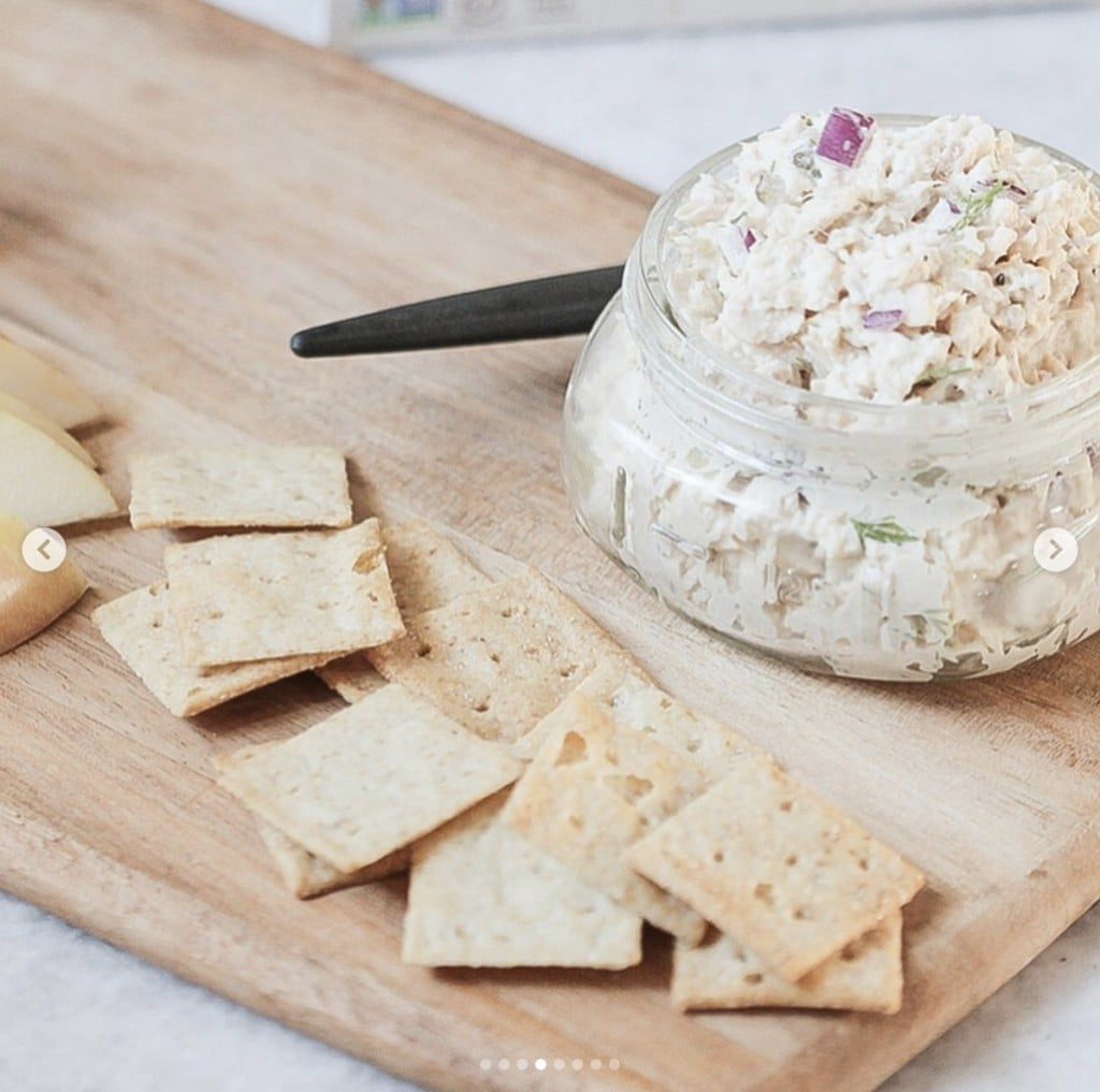 open jar of tuna salad on a wood cutting board with crackers on the side