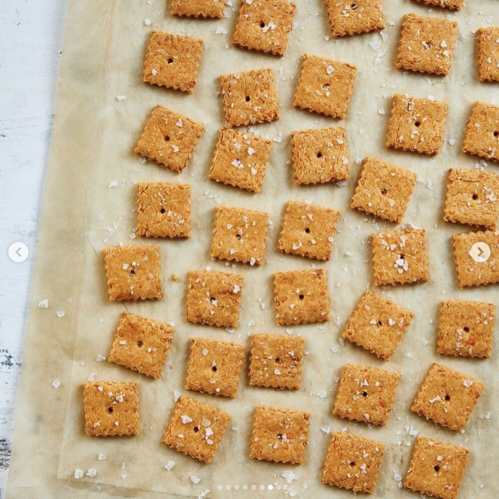 small square orange crackers sprinkled with coarse salt on parchment paper displayed on a white marble counter