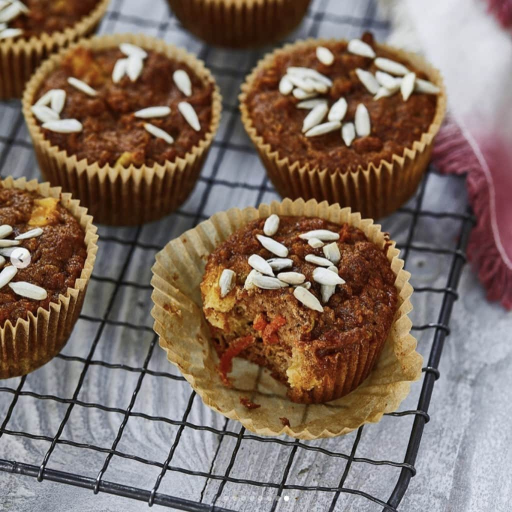 brown muffins topped with sunflower seeds in parchment paper cupcake wrappers cooling on a wire rack on a light gray wooden surface