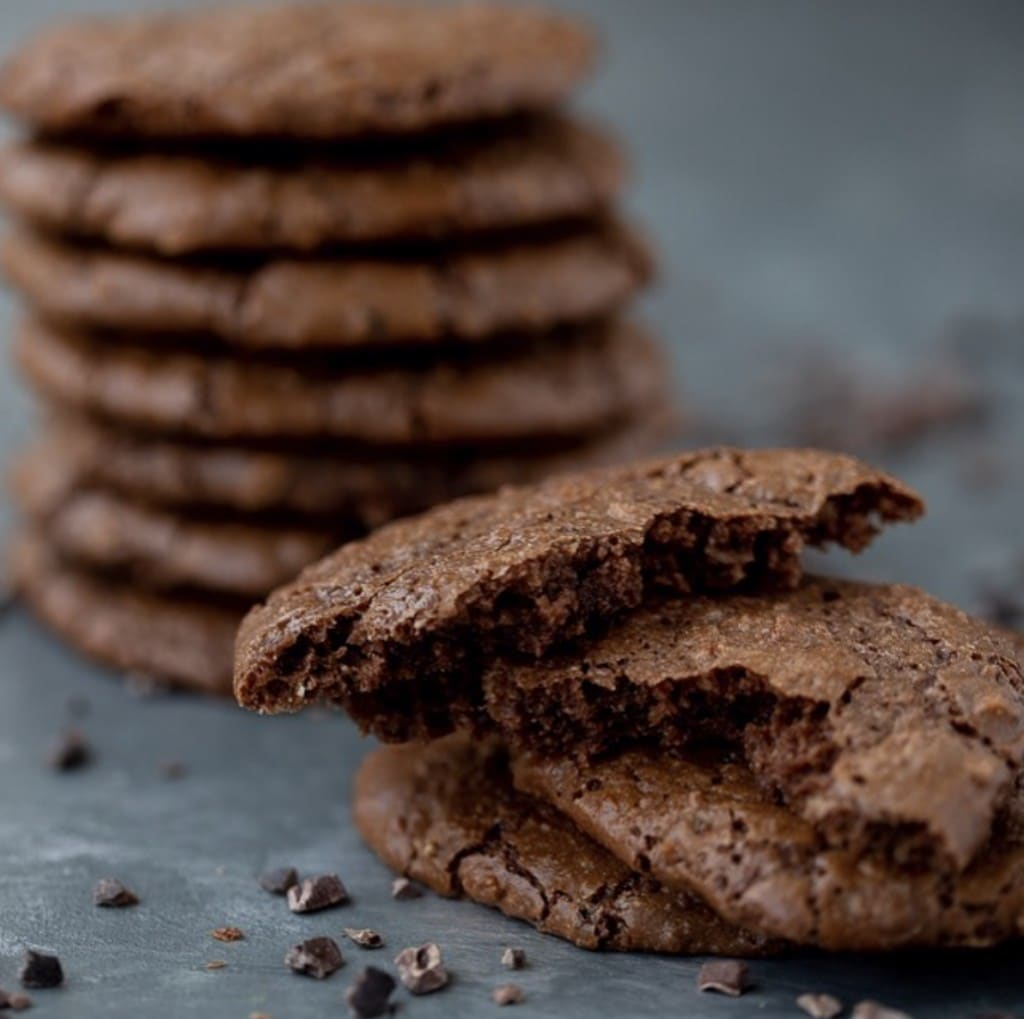 stacks of chocolate cookies displaying crinkle texture surrounded by cacao nibs displayed on a dark gray surface