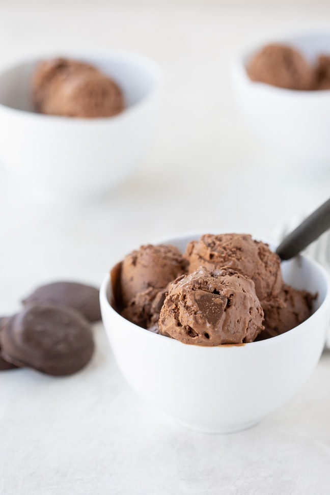 white bowl of double chocolate thin mint ice cream on a white surface. Thin mint cookies and additional ice cream filled bowls in background