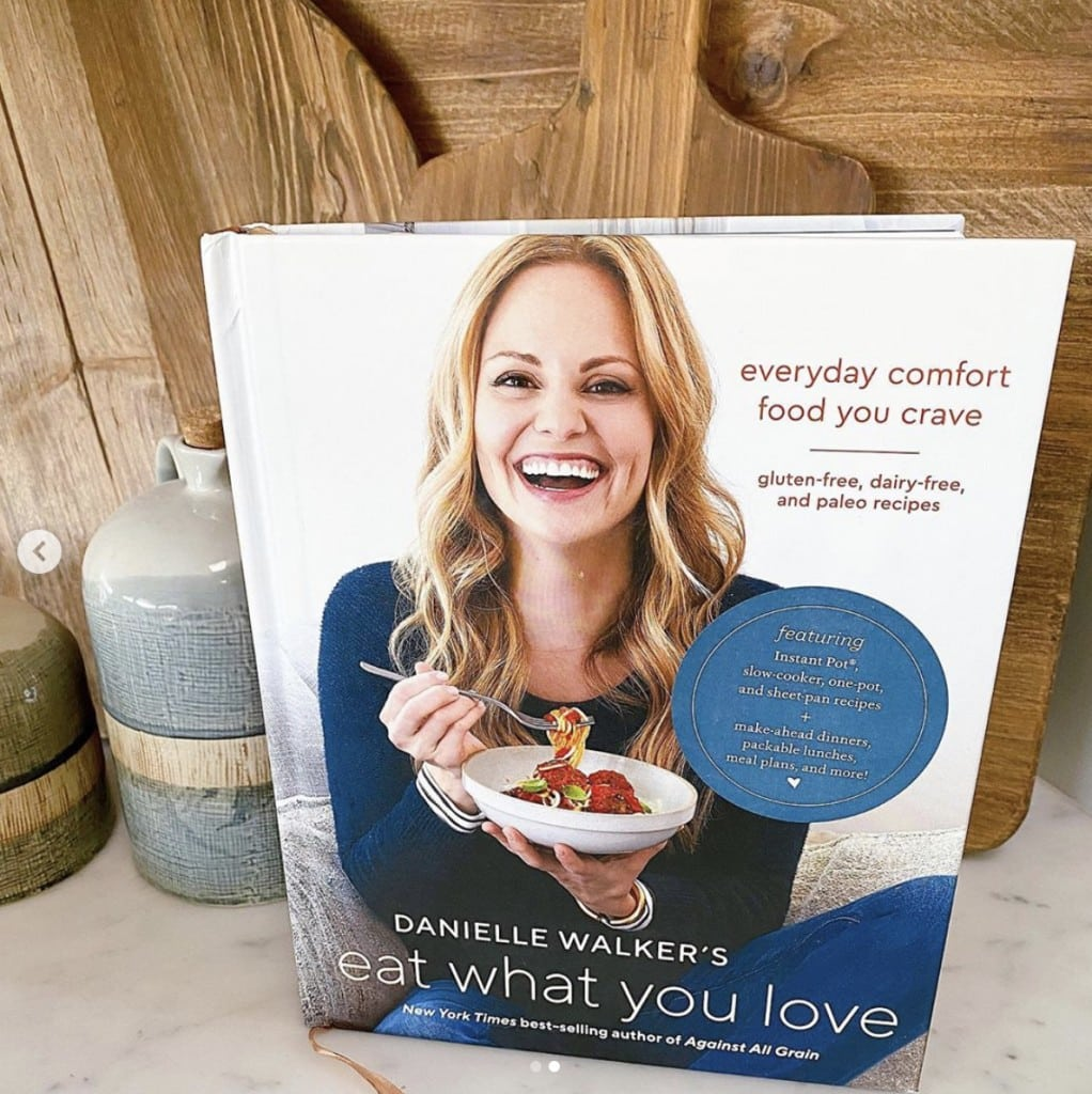 shot of Eat What You Love cookbook standing upright - book cover features Danielle Walker smiling at the camera while eating a bowl of pasta