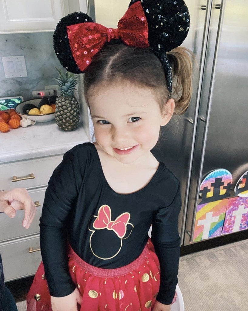 little girl stands in home kitchen and smiles at camera while wearing red and black Minnie Mouse outfit and sequin Minnie Mouse ears with a giant red bow
