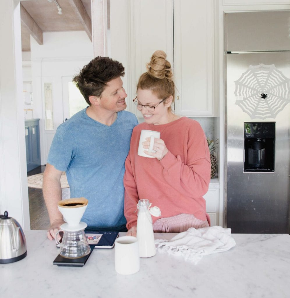 Man and woman stand in kitchen in close proximity enjoying a cup of coffee