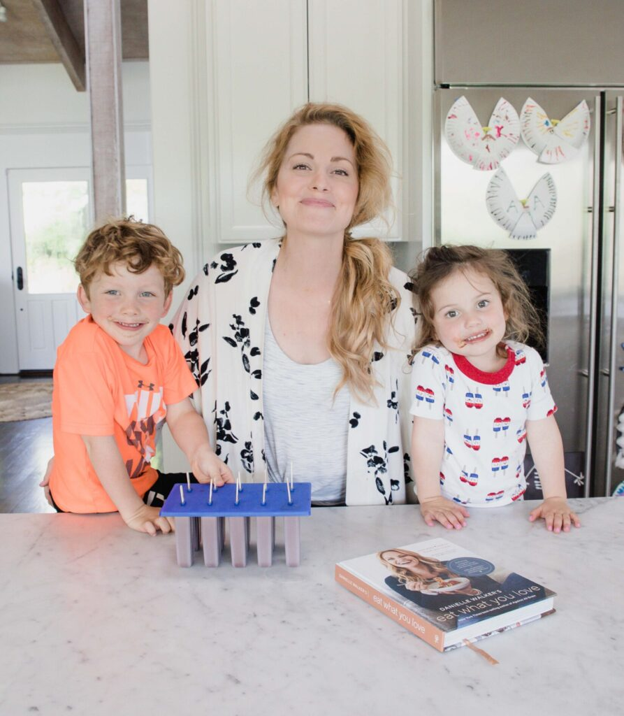 Mother and two children stand in home kitchen in front of freshly made fudge popsicles in mold and copy of Eat What You Love cookbook