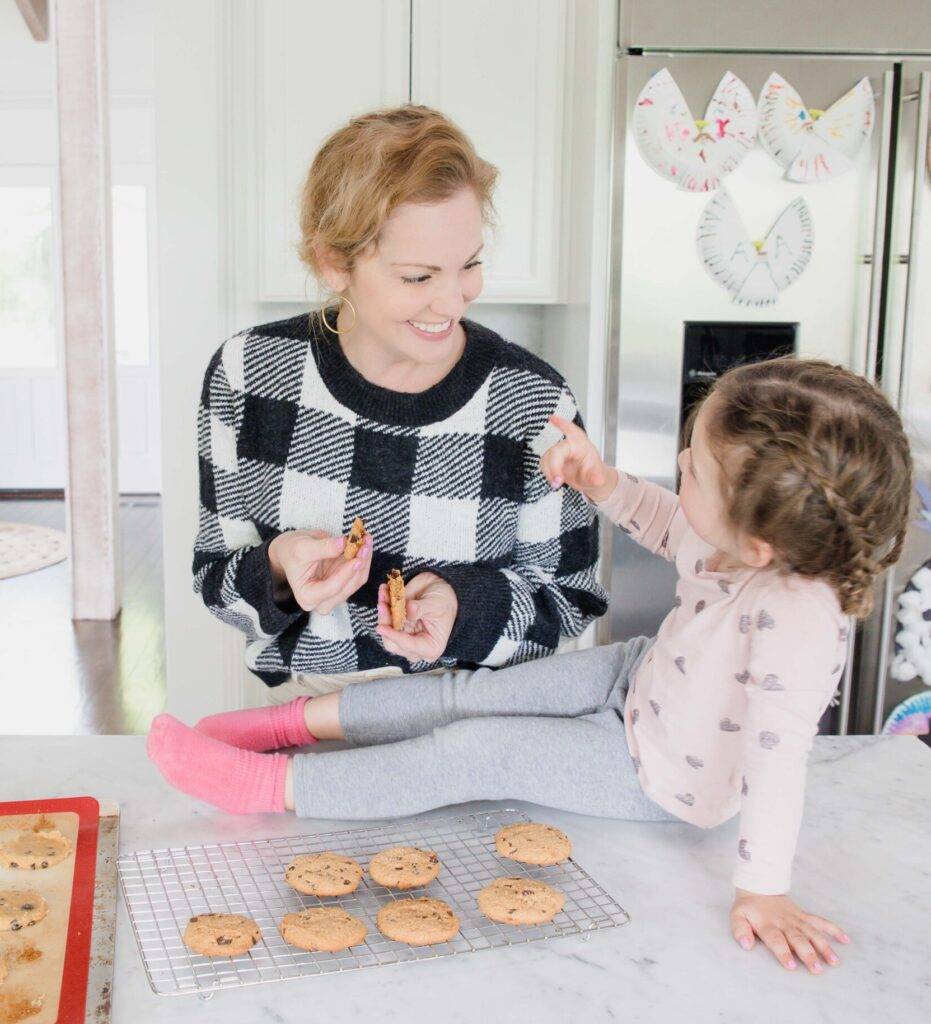 woman and young daughter hang in home kitchen bonding and smiling over freshly baked chocolate chip cookies