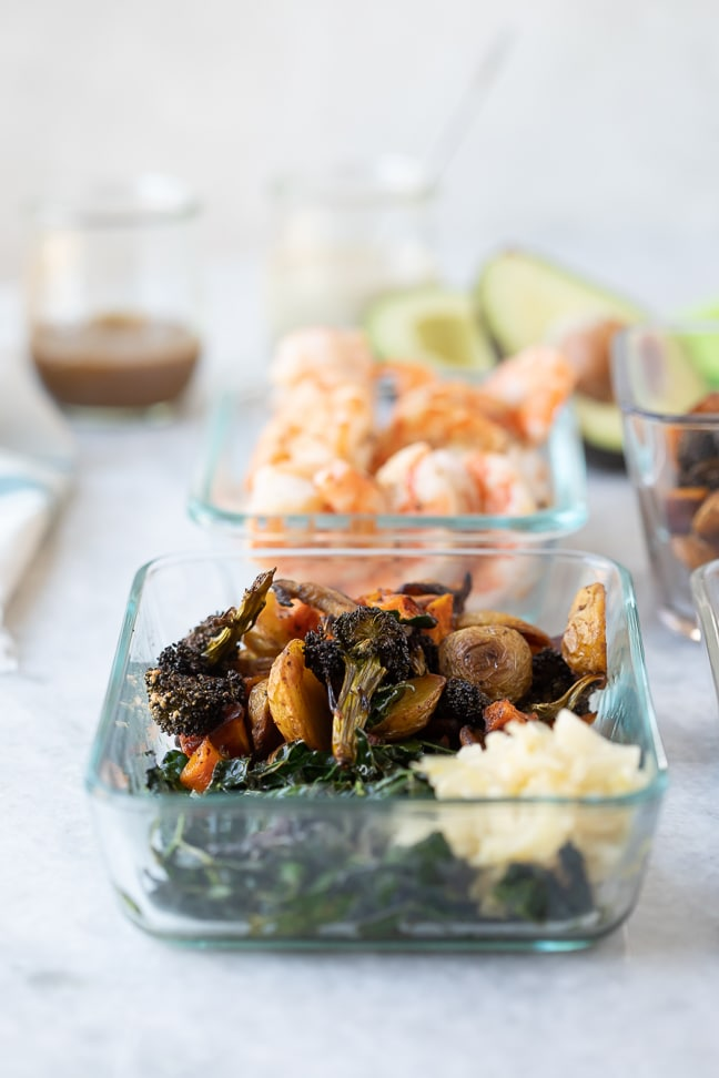 Roasted veggie bowl and a bowl of cooked shrimp displayed on a white marble counter