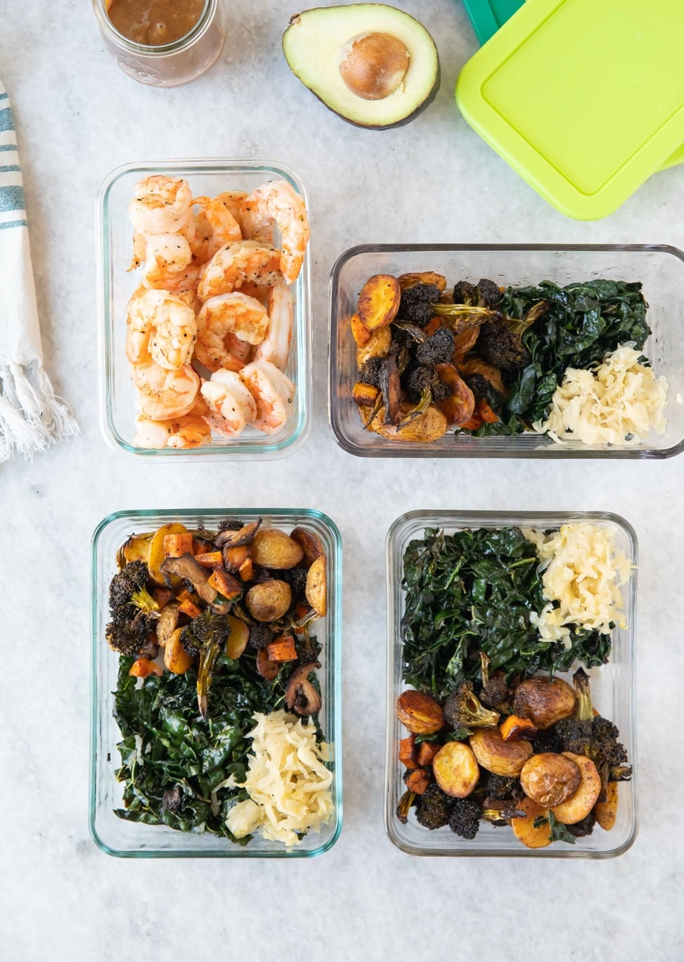 Roasted veggie bowls and a bowl of cooked shrimp displayed on a white marble counter