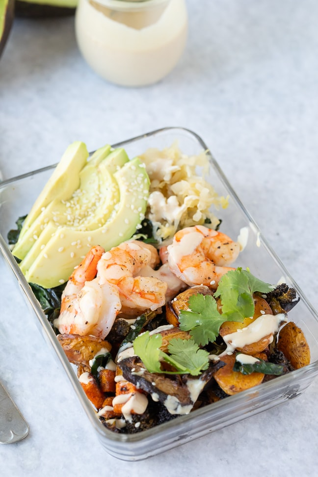 roasted veggie bowl topped with fresh avocado, cooked shrimp and homemade dressing