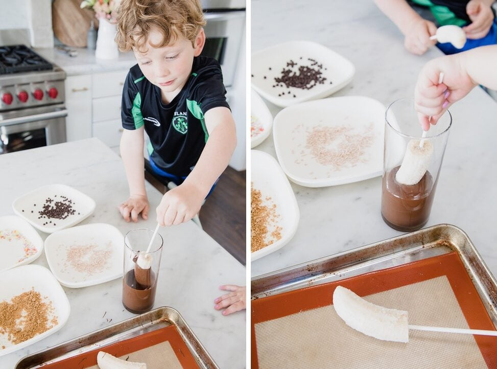 young boy carefully dips frozen bananas into melted chocolate in his home kitchen. A variety of toppings are on separate plates on the counter.