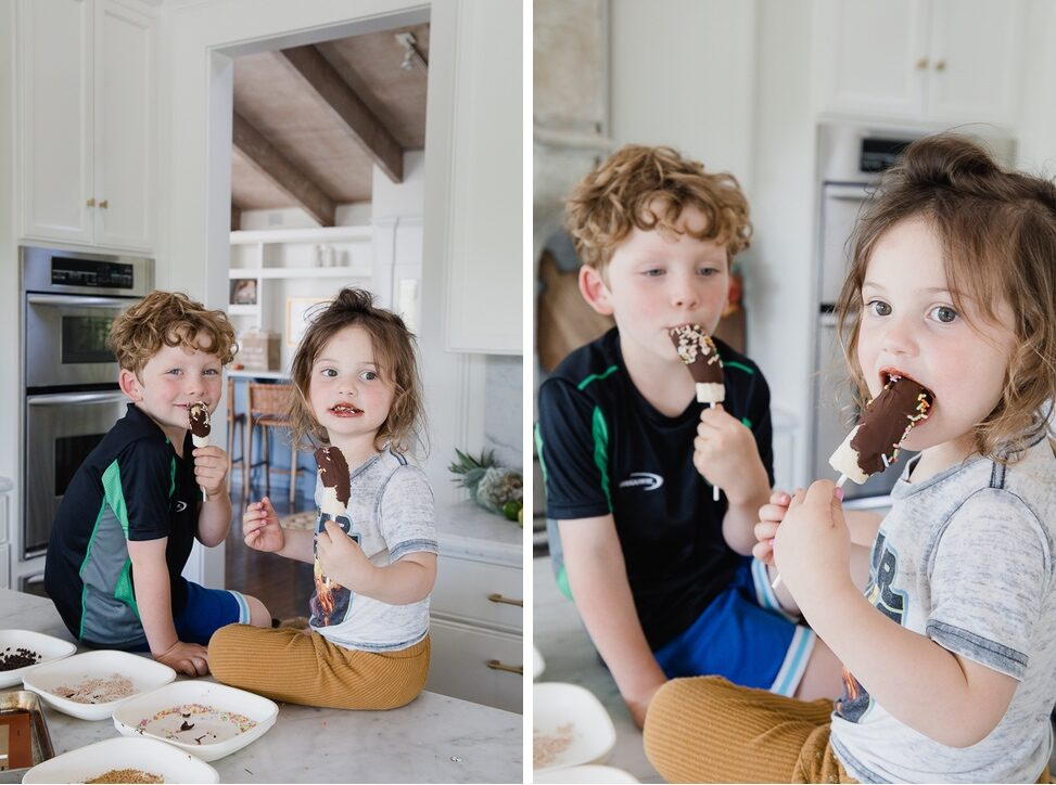 Children sit on home kitchen counter enjoying chocolate dipped bananas