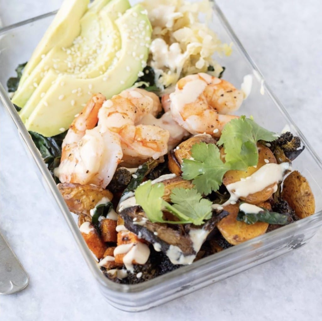 Up close view of roasted vegetables in a glass bowl - topped with fresh avocados, shrimp, fresh cilantro and a drizzle of tahini dressing